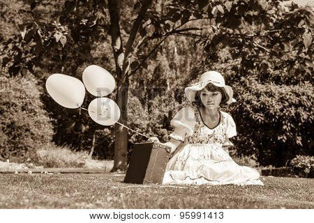Sad and disappointed young girl sitting with her suitcase alone in the garden.
