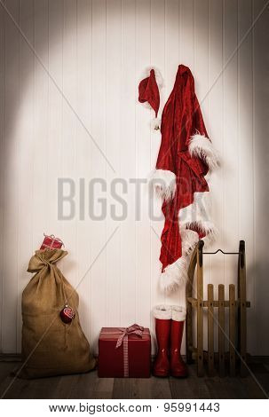Utensils of santa clause - jacket, hat, boots, sack and sledge. Wooden vintage christmas background with gifts in red and white.