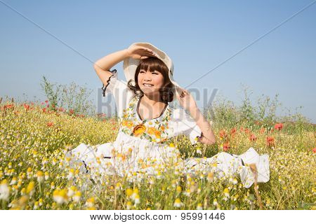 Happy young girl sitting in a flowery meadow in summertime.