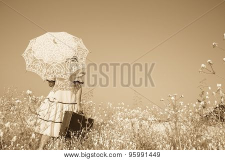 Nostalgic old photo in sepia color. Girl with her umbrella walking alone and searching her way.