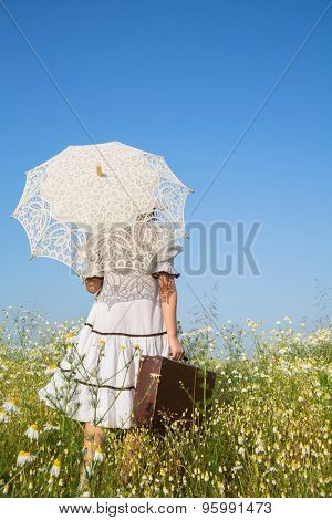 Walking girl in a flowery meadow. Blue sky concept background for summer times.