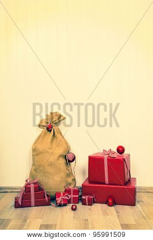 Old christmas backgrounds with the sack of santa and red gifts.