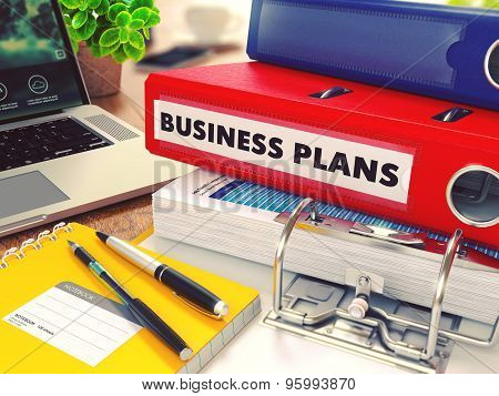 Business Plans on Red Office Folder. Toned Image.