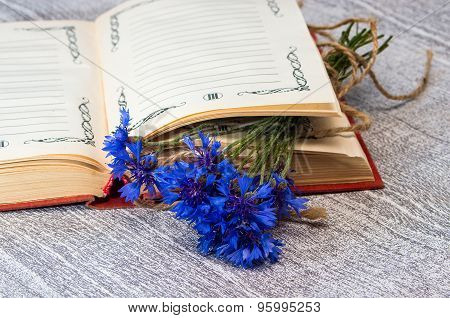Bouquet Of Blue Cornflowers On The Open Book.