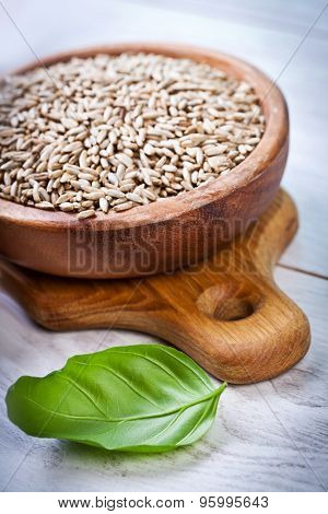 Bowl with Spelt on wooden background