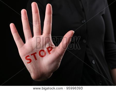 Female hand with word STOP on black background