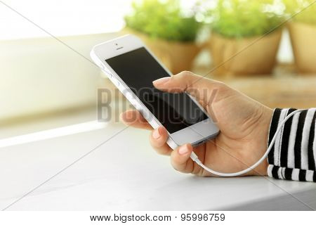 Music smartphone in female hand, on light background