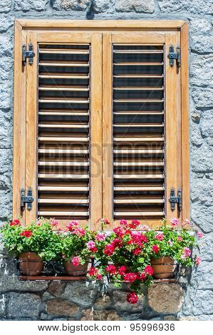 Typical Window Of A  Stone House With Wooden Shutters Closed And Colorful Flowers