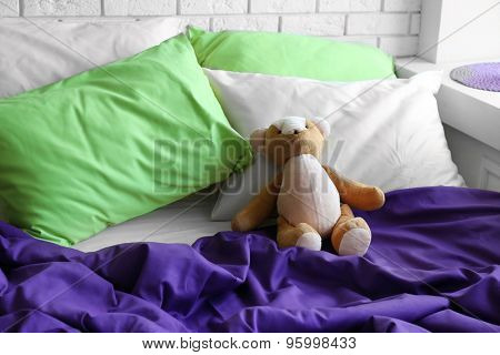 Comfortable bed with pillows and teddy bear in bedroom