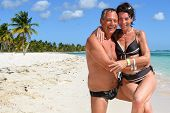 picture of crystal clear  - Loving couple on a beautiful deserted beach with turquoise and crystal clear waters of the Caribbean sea in the Dominican Republic on the island of Saonna - JPG