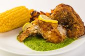 picture of grouper  - Closeup with selective focus on plate of fried grouper on bright green garlic and parsley pesto sauce - JPG