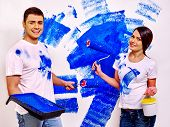 foto of messy  - Happy family in messy clothes paint wall at home - JPG