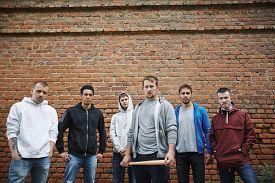 image of hooligan  - Group of hooligans or rappers on background of brick wall - JPG