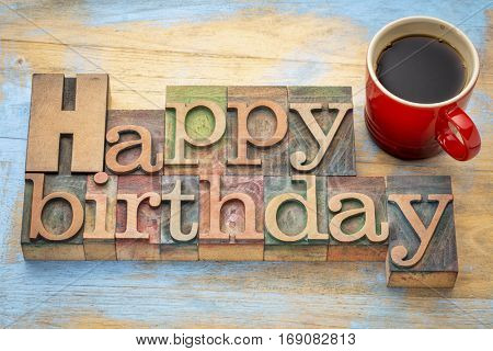 Happy Birthday greeting card - word abstract in vintage letterpress wood type blocks with a red stoneware cup of coffee