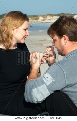 A Man Is Proposing To His Girlfriend On The Beach