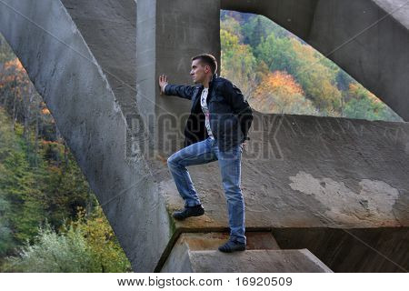 pensive guy standing on bridge of stone