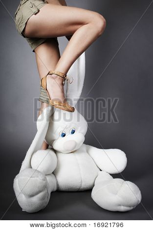 slim legs is trampling down fluffy toy