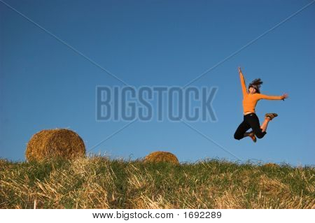 Woman Jumping In A Hay Bales Field