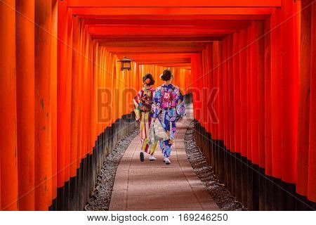 Women in traditional japanese kimonos walking at Fushimi Inari Shrine in Kyoto, Japan