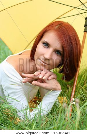beautiful girl relaxing on grass under yellow umbrella