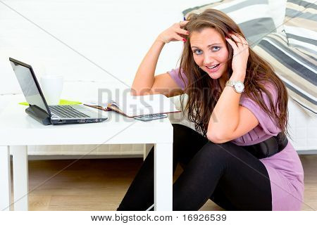 Stressed young housewife sitting on floor at home and calculate her expenses