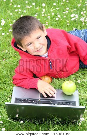 lindo niño con ordenador portátil en un prado