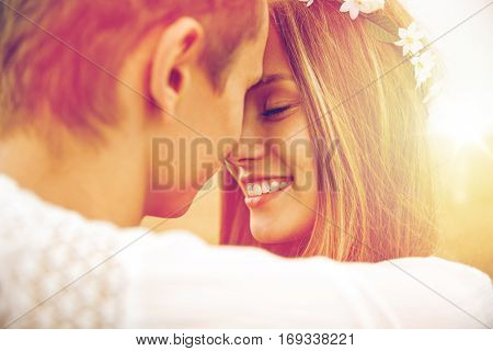 summer holidays, love, romance and people concept - happy smiling young hippie couple hugging outdoo