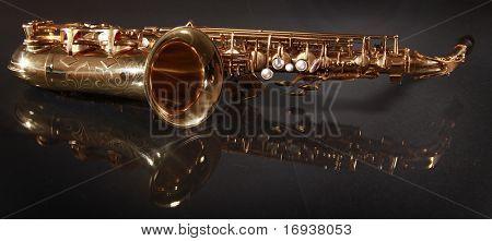 shiny golden saxophone on black background