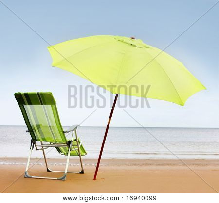 chair and green umbrella on the beach