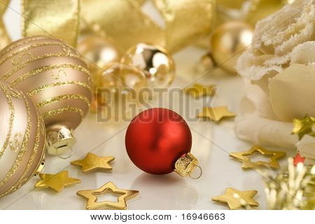 Red Christmas ball in the center of gold Christmas decorations. Selective focus