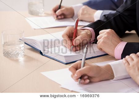 Three business people making notes. Close-up