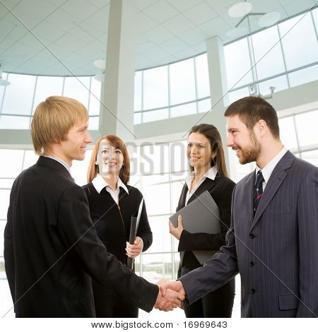 Businessmen shake their hands, two businesswomen look at them