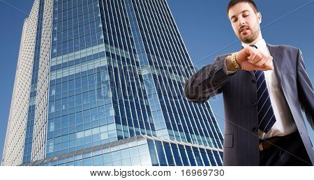 Un empresario mirando el reloj de pulsera contra un rascacielos