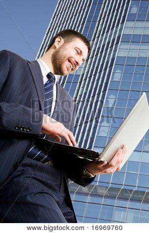 Walking businessman using his lap-top