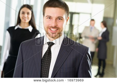 Happy young businessman  in an office environment