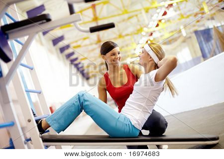 A girl pumping abdominal muscles in gym with help of her girlfriend