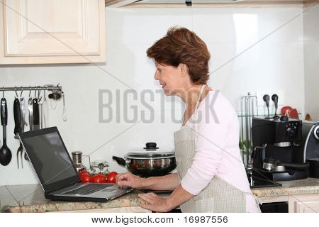 Closeup of senior woman in kitchen with laptop computer