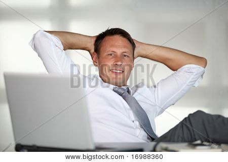 Businessman stretching arms in the office