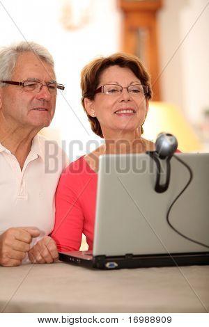Closeup of senior couple sending messages through web cam