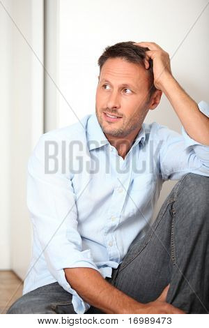 Closeup of man sitting on the floor at home