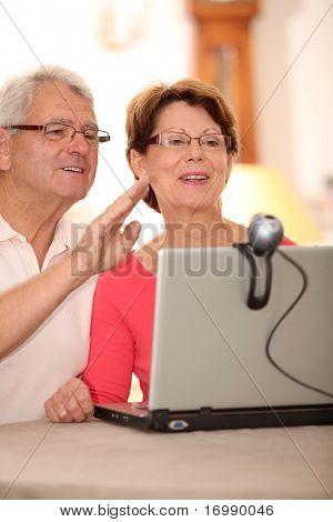 Closeup of senior couple sending messages through webcam
