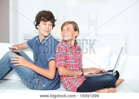 Teenagers with music player and computer at home