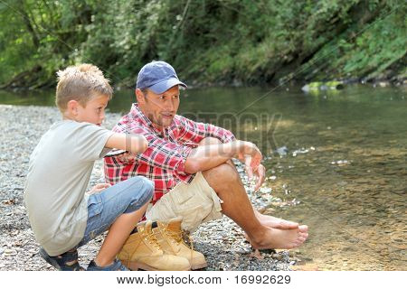 Father and son throwing pebble in river