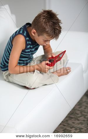 Little boy playing video games on sofa