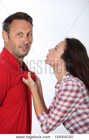 Angry woman pulling boyfriend shirt neck