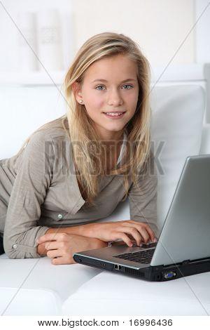 Blonde Mädchen sitzt im Sofa Surfen im internet