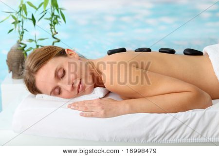 Beautiful woman with hot stones on her back