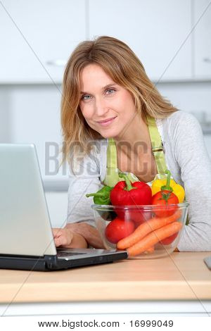 Woman in kitchen looking for cooking receipe
