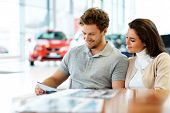 Beautiful young couple reading a booklet at the dealership showroom. poster