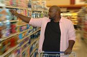 picture of grocery store  - Young man shopping at the store with an empty cart in front of him - JPG